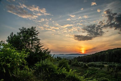 A colorful dawn breaks over the hills and forests of Berks County, PA in summer